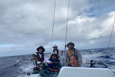 Crew wearing harnesses and flotation mid-ocean